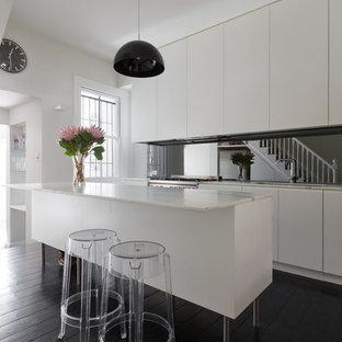 Diseño de cocina lineal, contemporánea, grande, abierta, con fregadero bajoencimera, armarios con paneles lisos, puertas de armario blancas, encimera de mármol, electrodomésticos de acero inoxidable, suelo de madera oscura, una isla, salpicadero con efecto espejo y suelo negro