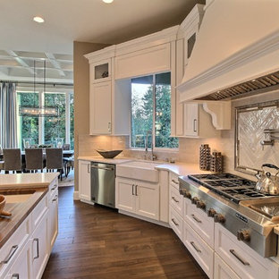 Huge transitional eat-in kitchen remodeling - Example of a huge transitional u-shaped dark wood floor eat-in kitchen design in Portland with an undermount sink, recessed-panel cabinets, white cabinets, quartzite countertops, white backsplash, ceramic backsplash, stainless steel appliances and two islands