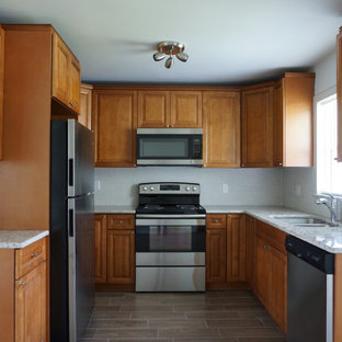 Photo of a small midcentury u-shaped eat-in kitchen in Orlando with a double-bowl sink, raised-panel cabinets, medium wood cabinets, granite benchtops, white splashback, mosaic tile splashback, stainless steel appliances, porcelain floors, no island, brown floor and green benchtop.