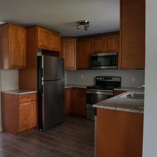 オーランドの小さいミッドセンチュリースタイルのおしゃれなキッチン (ダブルシンク、レイズドパネル扉のキャビネット、中間色木目調キャビネット、御影石カウンター、白いキッチンパネル、モザイクタイルのキッチンパネル、シルバーの調理設備の、磁器タイルの床、アイランドなし、茶色い床、緑のキッチンカウンター) の写真