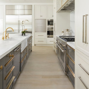 Large contemporary single-wall open plan kitchen in Salt Lake City with an undermount sink, recessed-panel cabinets, white cabinets, marble benchtops, white splashback, stone slab splashback, stainless steel appliances, light hardwood floors, multiple islands and beige floor.