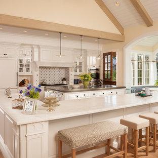 Esempio di un'ampia cucina classica con ante con riquadro incassato, ante bianche, top in marmo, paraspruzzi multicolore, elettrodomestici da incasso, parquet chiaro, 2 o più isole e pavimento marrone