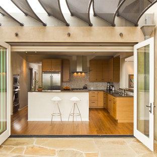 Mid-sized minimalist l-shaped medium tone wood floor eat-in kitchen photo in Santa Barbara with stainless steel appliances, medium tone wood cabinets, stone tile backsplash and an island