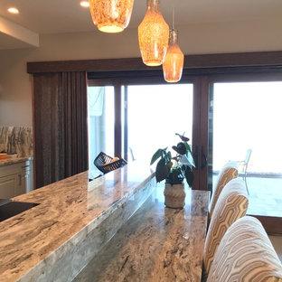 Idées déco pour une grande cuisine ouverte parallèle exotique avec un évier encastré, un placard avec porte à panneau surélevé, des portes de placard noires, un plan de travail en granite, une crédence grise, une crédence en dalle de pierre, un électroménager en acier inoxydable, un sol en carrelage de céramique, un îlot central, un sol beige et un plan de travail gris.