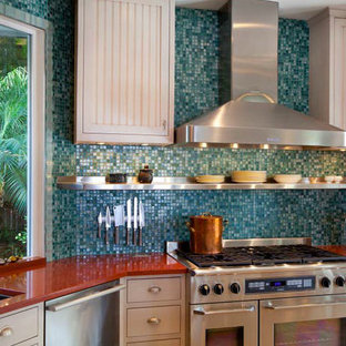 Design ideas for a mid-sized contemporary kitchen in Las Vegas with an undermount sink, white cabinets, solid surface benchtops, blue splashback, glass tile splashback, stainless steel appliances, no island and red benchtop.