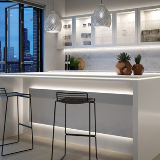 Contemporary galley kitchen/diner in Other with flat-panel cabinets, white cabinets, white splashback, light hardwood flooring, an island, beige floors and white worktops.