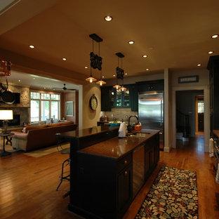 Immagine di una cucina boho chic di medie dimensioni con lavello sottopiano, ante a filo, ante nere, top in rame, paraspruzzi beige, paraspruzzi con piastrelle in ceramica, elettrodomestici in acciaio inossidabile, pavimento in legno massello medio e isola