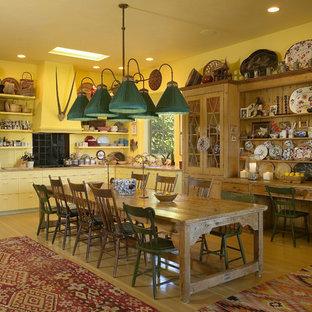 サンタバーバラのサンタフェスタイルのおしゃれなダイニングキッチン (黄色いキャビネット、黒い調理設備) の写真