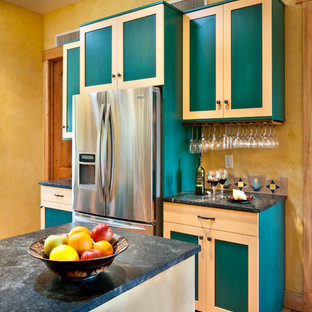 Mid-sized southwestern enclosed kitchen appliance - Enclosed kitchen - mid-sized southwestern u-shaped enclosed kitchen idea in Denver with a farmhouse sink, shaker cabinets, recycled glass countertops, multicolored backsplash, terra-cotta backsplash, stainless steel appliances and an island
