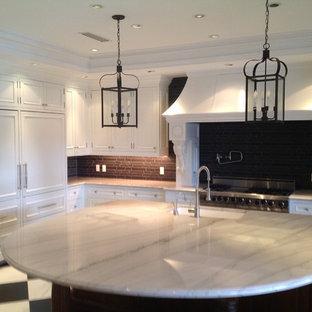 マイアミの大きいヴィクトリアン調のおしゃれなキッチン (アンダーカウンターシンク、レイズドパネル扉のキャビネット、白いキャビネット、御影石カウンター、黒いキッチンパネル、石タイルのキッチンパネル、シルバーの調理設備の、大理石の床) の写真