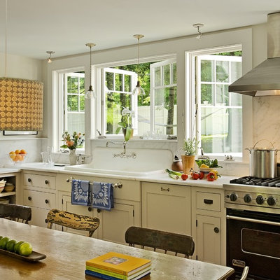 Inspiration for a timeless eat-in kitchen remodel in Burlington with a drop-in sink, beaded inset cabinets, marble countertops, white backsplash, stone slab backsplash, black appliances and beige cabinets