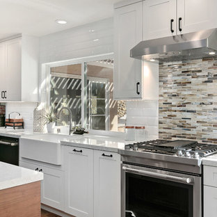 This is an example of a large transitional l-shaped open plan kitchen in San Diego with a farmhouse sink, shaker cabinets, white cabinets, quartz benchtops, multi-coloured splashback, ceramic splashback, stainless steel appliances, vinyl floors, with island, brown floor and grey benchtop.