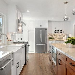 サンディエゴの大きいトランジショナルスタイルのおしゃれなキッチン (エプロンフロントシンク、シェーカースタイル扉のキャビネット、白いキャビネット、クオーツストーンカウンター、マルチカラーのキッチンパネル、セラミックタイルのキッチンパネル、シルバーの調理設備の、クッションフロア、茶色い床、グレーのキッチンカウンター) の写真