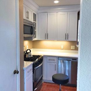 ヒューストンの中サイズのトラディショナルスタイルのおしゃれなキッチン (エプロンフロントシンク、シェーカースタイル扉のキャビネット、白いキャビネット、シルバーの調理設備の、アイランドなし、赤い床、珪岩カウンター、白いキッチンパネル、石スラブのキッチンパネル) の写真