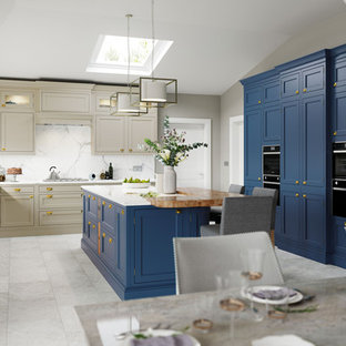 Photo of a transitional u-shaped eat-in kitchen in Other with shaker cabinets, blue cabinets, wood benchtops, white splashback, black appliances, with island, white floor and beige benchtop.