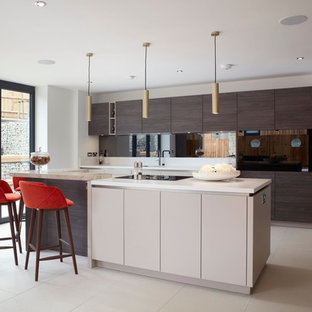 Photo of a large contemporary u-shaped kitchen in Kent with black appliances, an island, white floors, white worktops, flat-panel cabinets and brown cabinets.