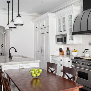 Eat-in kitchen - large traditional galley dark wood floor eat-in kitchen idea in Chicago with glass-front cabinets, white cabinets, quartzite countertops, white backsplash, subway tile backsplash, stainless steel appliances and an island