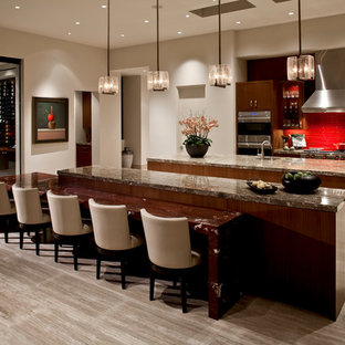 Inspiration for a large contemporary single-wall open plan kitchen in San Diego with flat-panel cabinets, medium wood cabinets, marble benchtops, red splashback, glass tile splashback, stainless steel appliances, multiple islands, a single-bowl sink, travertine floors and beige floor.