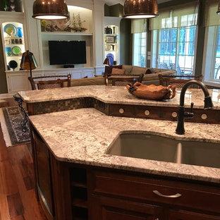 他の地域の中サイズのトラディショナルスタイルのおしゃれなキッチン (アンダーカウンターシンク、レイズドパネル扉のキャビネット、中間色木目調キャビネット、御影石カウンター、グレーのキッチンパネル、石タイルのキッチンパネル、シルバーの調理設備の、無垢フローリング、赤い床、マルチカラーのキッチンカウンター) の写真