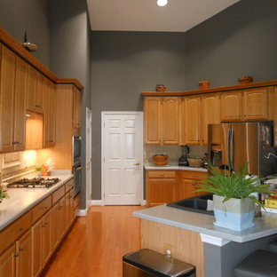Large transitional open concept kitchen photos - Example of a large transitional u-shaped medium tone wood floor open concept kitchen design in DC Metro with a double-bowl sink, raised-panel cabinets, light wood cabinets, solid surface countertops, beige backsplash, porcelain backsplash, stainless steel appliances and an island