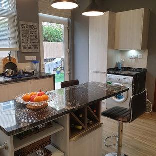 他の地域の中サイズのモダンスタイルのおしゃれなキッチン (フラットパネル扉のキャビネット、ベージュのキャビネット、大理石カウンター、ベージュキッチンパネル、セラミックタイルのキッチンパネル、クッションフロア、茶色い床、黒いキッチンカウンター) の写真