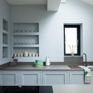 Réalisation d'une cuisine parallèle design avec un évier encastré, un placard à porte shaker et des portes de placard bleues.