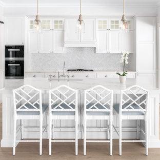 Beach style kitchen in Brisbane with white cabinets, marble benchtops, grey splashback, mosaic tile splashback, light hardwood floors and a peninsula.