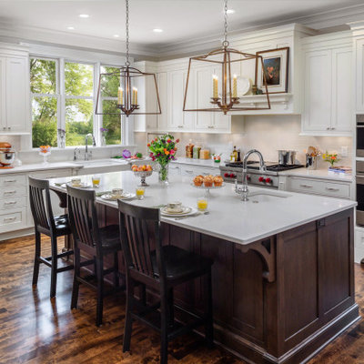 Elegant l-shaped dark wood floor and brown floor kitchen photo in Milwaukee with a farmhouse sink, shaker cabinets, white cabinets, gray backsplash, subway tile backsplash, stainless steel appliances, an island and white countertops
