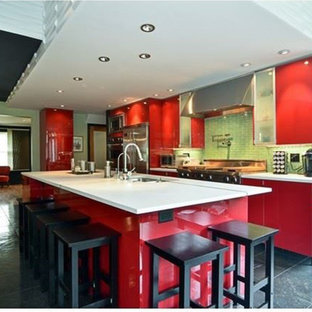 Mid-sized contemporary open concept kitchen designs - Inspiration for a mid-sized contemporary l-shaped slate floor and multicolored floor open concept kitchen remodel in Chicago with an undermount sink, flat-panel cabinets, red cabinets, concrete countertops, green backsplash, glass tile backsplash, stainless steel appliances and an island