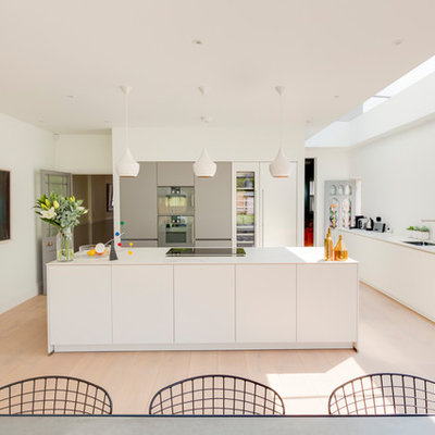 Large trendy beige floor eat-in kitchen photo in London with an undermount sink, flat-panel cabinets, white cabinets, stainless steel appliances, an island and white countertops