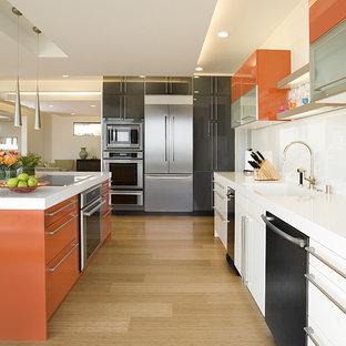 Удачное сочетание для дизайна помещения: параллельная кухня среднего размера в современном стиле с техникой из нержавеющей стали, монолитной раковиной, плоскими фасадами, оранжевыми фасадами, обеденным столом, белым фартуком, полом из бамбука и бежевым полом - самое интересное для вас