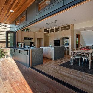 Foto di una cucina contemporanea di medie dimensioni con ante lisce, ante in legno chiaro, top in vetro riciclato, elettrodomestici neri, parquet chiaro, isola, paraspruzzi rosso, paraspruzzi con piastrelle di vetro e lavello sottopiano