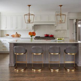 Foto på ett stort vintage beige l-kök, med vita skåp, marmorbänkskiva, vitt stänkskydd, stänkskydd i keramik, rostfria vitvaror, mellanmörkt trägolv, en köksö, brunt golv och skåp i shakerstil