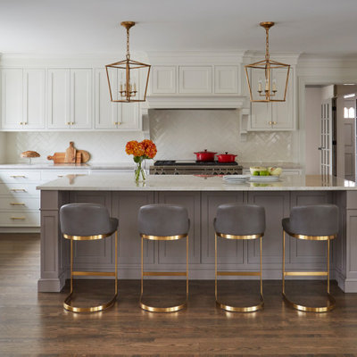 Large transitional l-shaped medium tone wood floor and brown floor kitchen photo in Chicago with white cabinets, marble countertops, white backsplash, ceramic backsplash, stainless steel appliances, an island, beige countertops and shaker cabinets