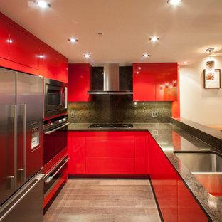 バンクーバーの中サイズのエクレクティックスタイルのおしゃれなキッチン (ダブルシンク、フラットパネル扉のキャビネット、赤いキャビネット、クオーツストーンカウンター、黒いキッチンパネル、シルバーの調理設備の、濃色無垢フローリング) の写真