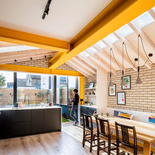 Contemporary l-shaped kitchen/diner in London with flat-panel cabinets, black cabinets, wood worktops, green splashback, stainless steel appliances, medium hardwood flooring and no island.