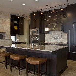 Foto de cocina actual con electrodomésticos con paneles y salpicadero de piedra caliza