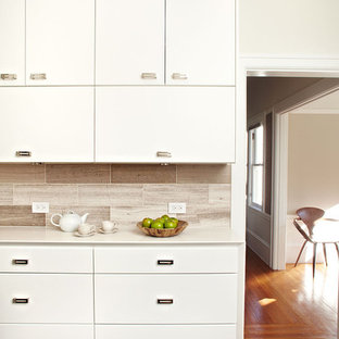 Example of a small trendy l-shaped ceramic floor enclosed kitchen design in San Francisco with flat-panel cabinets, white cabinets, quartz countertops, gray backsplash, stone tile backsplash, stainless steel appliances and no island