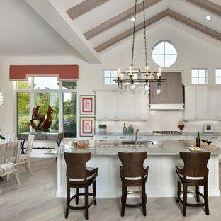 Cette image montre une grande cuisine américaine ethnique avec des portes de placard blanches, un plan de travail en granite, une crédence blanche, un électroménager en acier inoxydable, un sol en bois clair, un îlot central et un placard à porte shaker.