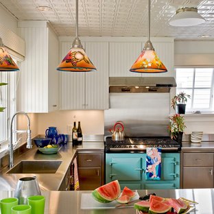 Inspiration for a beach style kitchen in Portland Maine with an integrated sink, stainless steel cabinets, stainless steel benchtops, coloured appliances, flat-panel cabinets, metallic splashback and metal splashback.
