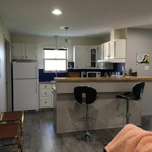 他の地域の小さいトラディショナルスタイルのおしゃれなコの字型キッチン (インセット扉のキャビネット、白いキャビネット、タイルカウンター、青いキッチンパネル、セラミックタイルのキッチンパネル、ラミネートの床、グレーの床、青いキッチンカウンター) の写真