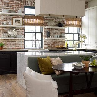 ヒューストンの広いトランジショナルスタイルのおしゃれなキッチン (エプロンフロントシンク、大理石カウンター、レンガのキッチンパネル、シルバーの調理設備、淡色無垢フローリング、インセット扉のキャビネット、黒いキャビネット、マルチカラーのキッチンパネル、ベージュの床) の写真