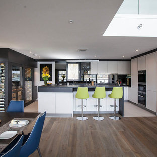 This is an example of an expansive contemporary u-shaped open plan kitchen in Essex with flat-panel cabinets, white cabinets, an island, black worktops, black appliances and white floors.