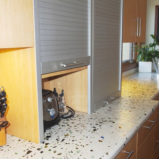 Large modern single-wall eat-in kitchen in San Diego with flat-panel cabinets, light wood cabinets, recycled glass benchtops, glass tile splashback, with island, beige splashback and stainless steel appliances.