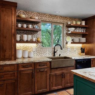 他の地域の中サイズのトランジショナルスタイルのおしゃれなキッチン (フラットパネル扉のキャビネット、茶色いキャビネット、御影石カウンター、ベージュキッチンパネル、黒い調理設備、テラコッタタイルの床、赤い床、ベージュのキッチンカウンター、エプロンフロントシンク、セメントタイルのキッチンパネル) の写真