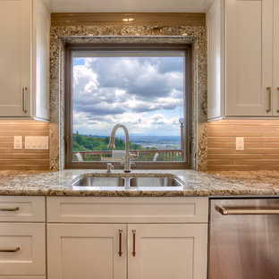 Transitional kitchen designs - Example of a transitional medium tone wood floor kitchen design in Seattle with an undermount sink, shaker cabinets, white cabinets, granite countertops, brown backsplash, stainless steel appliances and a peninsula