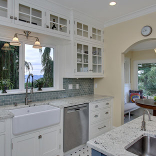 Photo of an arts and crafts eat-in kitchen in Seattle with a farmhouse sink, glass-front cabinets, white cabinets, granite benchtops, blue splashback, glass tile splashback, stainless steel appliances, ceramic floors and with island.