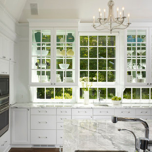 Example of a large classic u-shaped medium tone wood floor enclosed kitchen design in Chicago with glass-front cabinets, white cabinets, quartzite countertops, stainless steel appliances, an island and an undermount sink