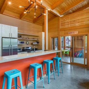 Diseño de cocina marinera, abierta, con armarios con paneles lisos, puertas de armario de madera clara, salpicadero de madera, electrodomésticos de acero inoxidable, suelo de cemento, una isla y suelo gris