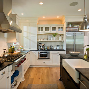 Example of a mid-sized classic l-shaped light wood floor enclosed kitchen design in Boston with a farmhouse sink, white backsplash, subway tile backsplash, stainless steel appliances, shaker cabinets, white cabinets, solid surface countertops and an island
